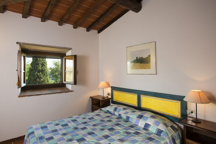 One of the bedrooms in the Borgo apartments with view of the surrounding Tuscan countryside