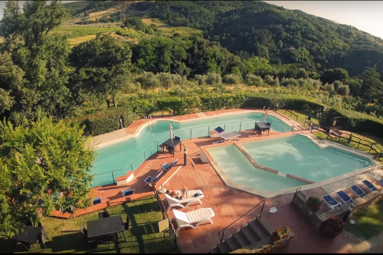 View from above of the two pools surrounded by the green of the hillside on which Borgo La Casaccia sits