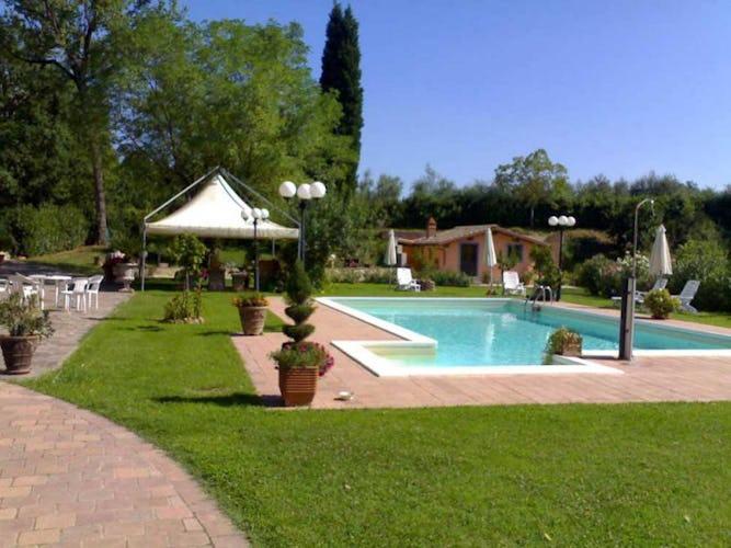 La piscina con la zona solarium, ombrelloni, sdraio e gazebo