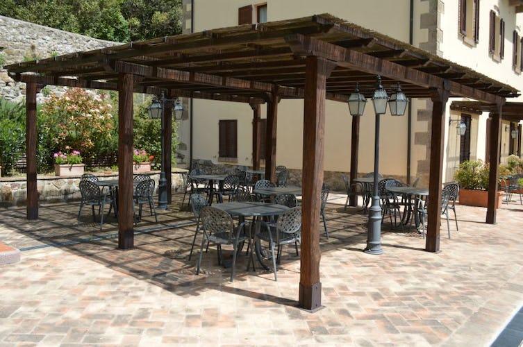 Il pergolato in legno con tavoli e sedie per mangiare all'aperto