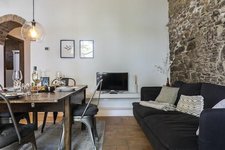 Il soggiorno dell'appartamento Capanne, con le pareti in pietra a vista