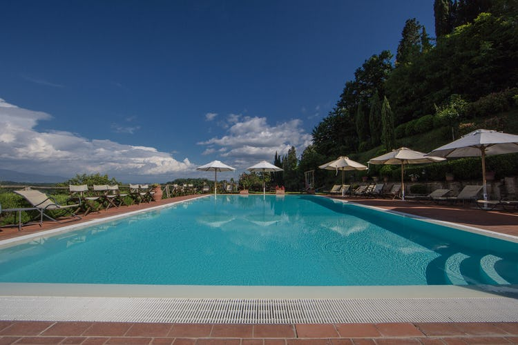 Residence Il Gavillaccio - relaxing poolside area with deck chairs, tables and umbrellas